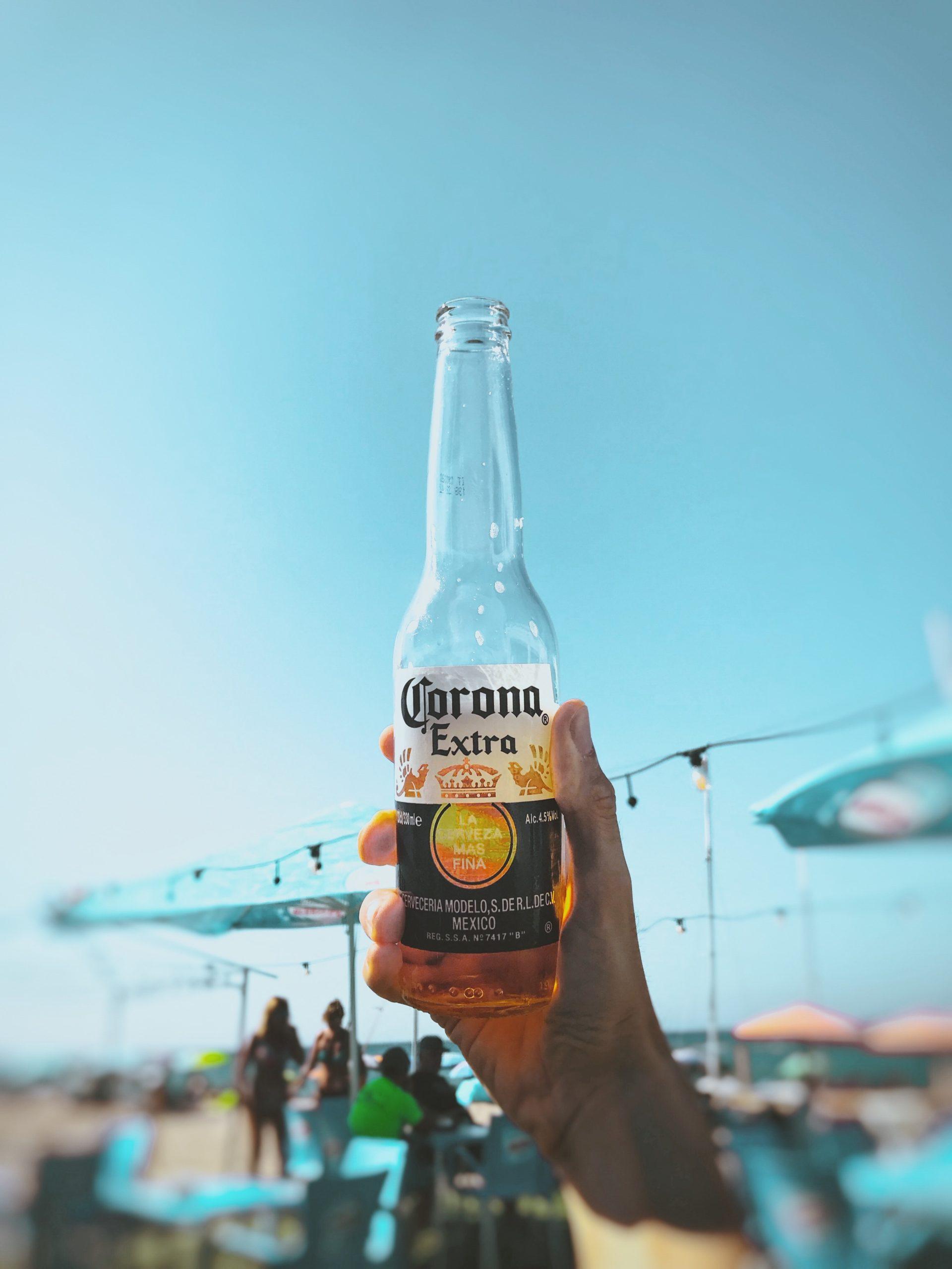 Person hält Bier der Marke Corona